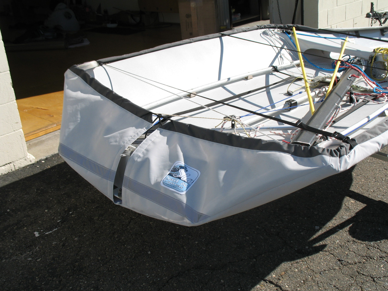 """29'er Sailboat Hull Cover by SLO Sail and Canvas. 1/4"""" shockcord is built into cover to secure your cover tightly around the boat's rubrail."""