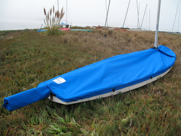 """Sunfish Mast Up Flat Cover made in America by skilled artisans at SLO Sail and Canvas.  1/4"""" shockcord is built into cover to secure your cover tightly around the boat's rubrail. Webbing loops are sewn around the perimeter of our top covers allowing your cover to be tied to your boat. A mast collar fits tightly around your boat's mast. All of our covers are patterned from the actual boats they are designed to fit. This make for a better, higher quality product."""