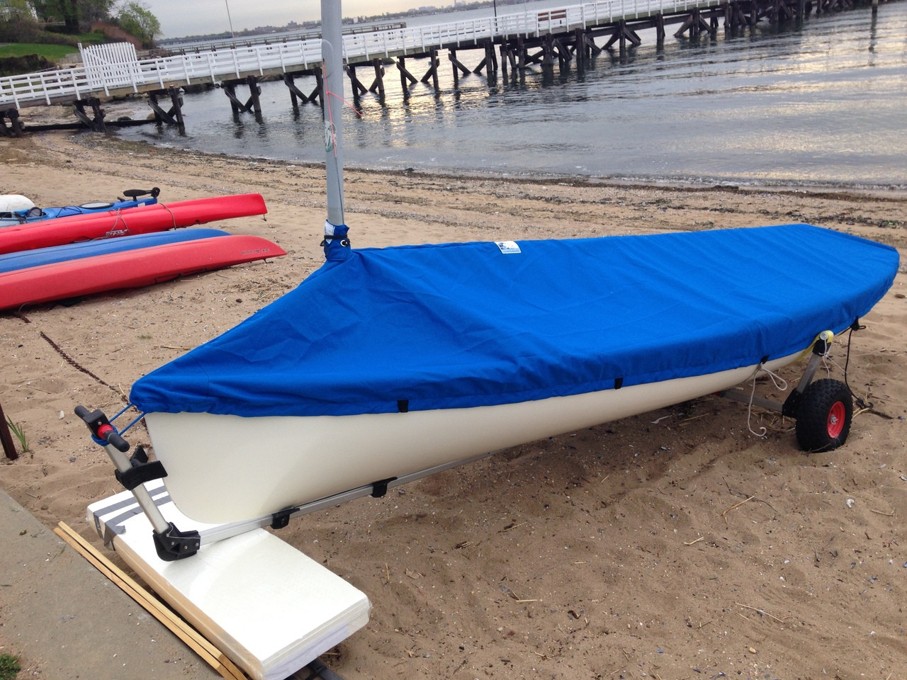 "Finn sailboat Mast Up Peaked Mooring Cover made in America by skilled artisans at SLO Sail and Canvas. Shown in Sunbrella Pacific Blue. 1/4"" shockcord is built into cover to secure your cover tightly around the boat's rubrail. Web Loops allow you to ""tent"" your cover up to prevent pooling of water.  Available in 3 fabrics and many color choices. All of our covers are patterned from the actual boats they are designed to fit. This make for a better, higher quality product."