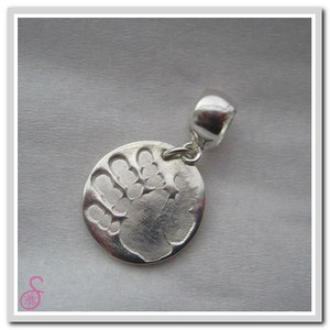 A Sterling Silver circular handprint charm with optional Pandora-type attachment
