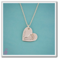 A single Sterling Silver heart-shaped footprint necklace