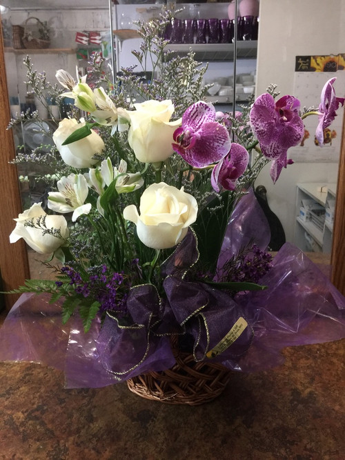 A live orchid is the feature of this statement arrangement.  We accent it with white roses, peruvian lilies, limonium and wax flower and bundle it all up with a luxurious purple ribbon