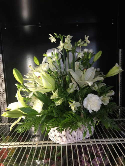 Soothing, calming is this peaceful arrangement of lilies and carnations, nestled in a white basket amid various greens.