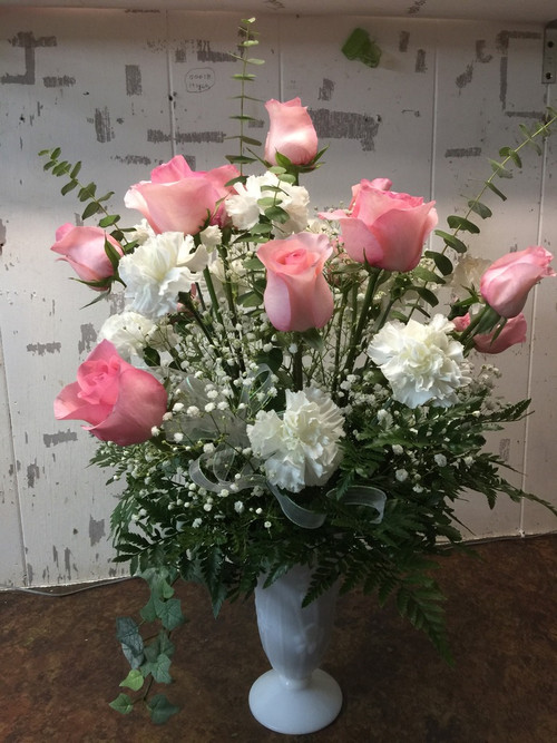 Lush and lovely arrangement of pink roses and white carnations inbedded in a mound of various greens shows your love in the best light.
