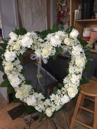 Express your loving memory with this all white heart shaped easel, showcasing roses, carnations, mums and monte casino
