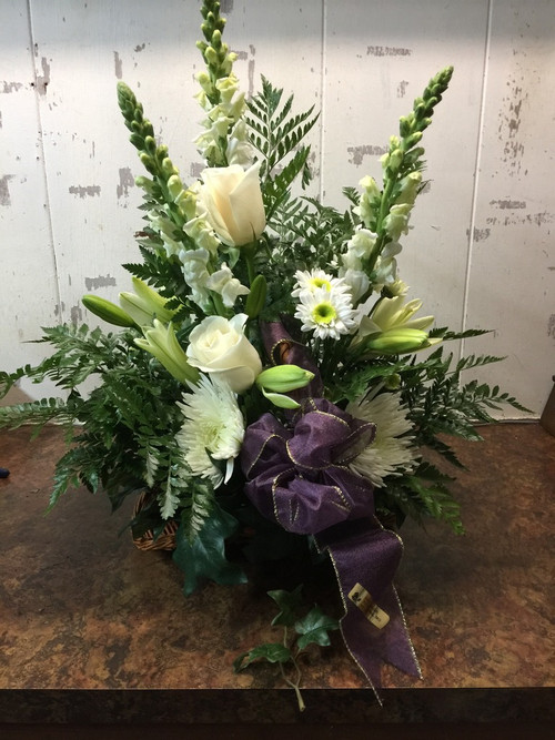 Lush Basket full of white roses, snap dragons, spider mums and lilies and garnished with a purple ribbon will show your respects in the most refined way.