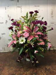Sympathy spray featuring pink lilies and an assortment of purple and pink flowers arranged in spray form and accented with a purple ribbon.
