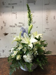 Express your sympathy with this peaceful arrangement of lilies, carnations, peruvian lilies and snap dragons in a white basket and accented with a tulle ribbon.