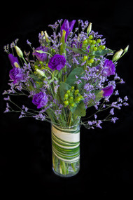 This cool as a cucumber arrangement will soothe and please even the most discerning recipient.   An aspidistra leaf shows off submerged in the vase and topped with elegant purple lisianthus, purple iris and limonium.  Sure to please.