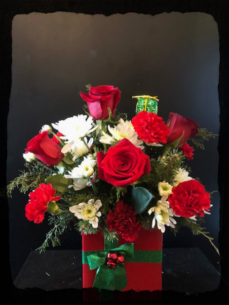 The perfect Christmas Present - beautiful red and white roses, carnations, poms and Christmas greens arranged in a keepsake ceramic vase, adorned with a green bow and red bells