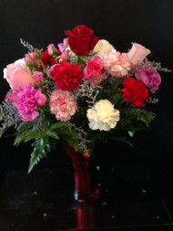 Luscious concoction of red and pink roses interspersed with a dozen long lasting carnations and accented with limonium in our classic red vase is sure to please.