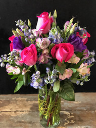 Lush collection of hot piink roses, purple lisianthus, blue delphinium and peruvian lilies
