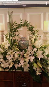 Elegant and impressive fresh floral display surrounding urn of your beloved, featuring white lilies.