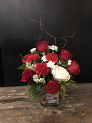 Red and white roses and carnations in a snow flocked, winterberry cube will brighten up their Christmas.