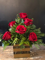 1/2 Doz red roses nestled among Christmas greens in an elegant gold striped rectangular vase.