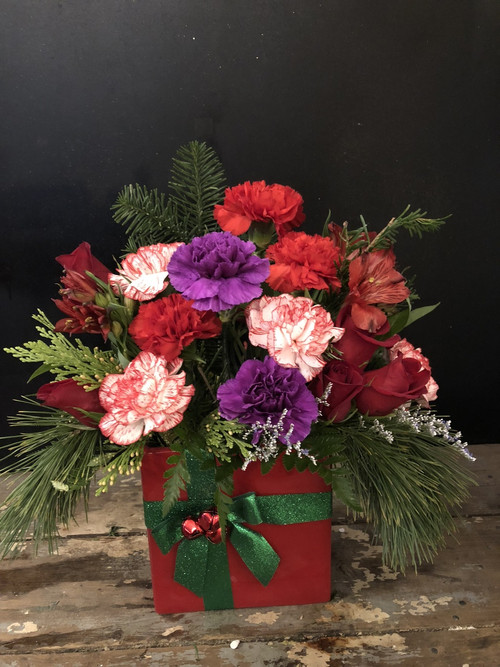 Classic red  roses, carnations and alstromeria with a pop of purple in our red and green Christmas present vase