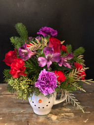Don't have to rob the bank to send this oversize snowman mug decorated in purple and red roses, carnations  and peruvian lilies amid a bed of Christmas greens.