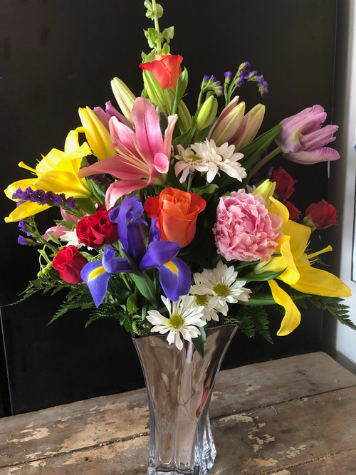 A glorious collection of upscale spring flowers including peonies, parrot tulips, iris, lilies, lisianthus and roses, all arranged in a mirrored designer vase.