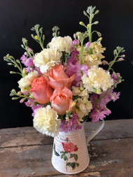 A delicious concoction of sweet smelling stock, roses and carnations in keepsake floral pitcher