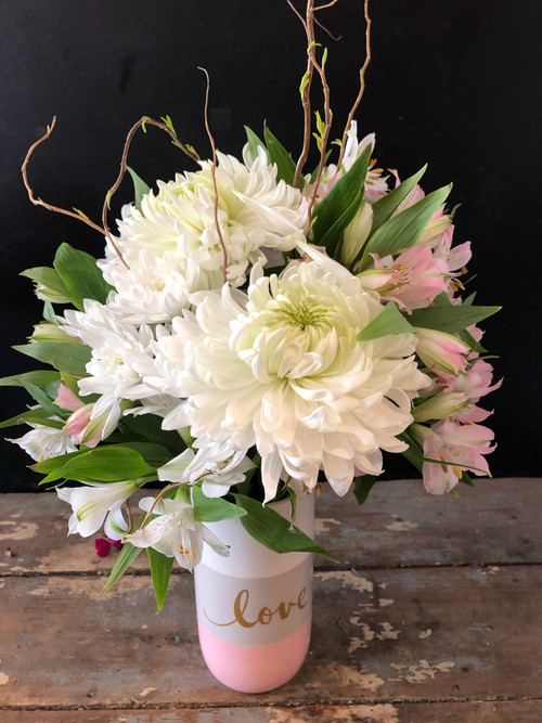 Shower her with delicate peruvian lilies and huge football mums  merged to create a picturesque arrangement that she will love.  This also works beautifully for a new baby girl and we also have the same vase in blue for a new baby boy.