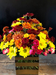 Assorted fall flowers arranged in a gold striped rectangular vase will be sure to brighten up someone's day.