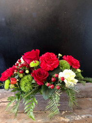Red and green roses, carnations and dianthus in a woodtone planter make a warm centerpiece for your christmas table.