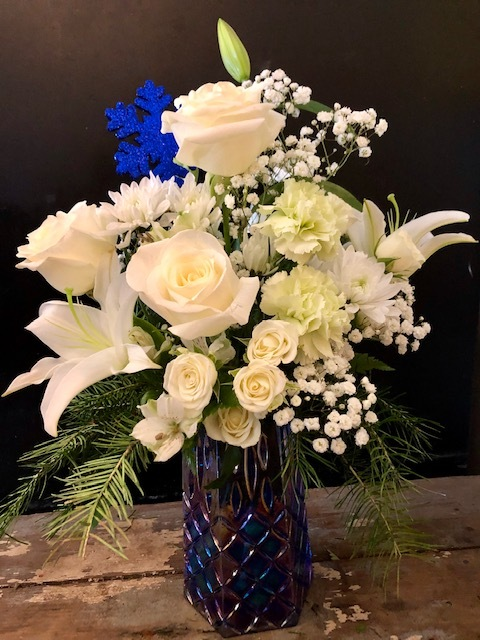 Elegant is the word for this mesmerizing mixture of white lilies, roses, chrysanthemums and babies breath, adorned with a glittery blue snowflake in a gorgeous blue mosaic vase