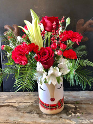 Cute and Quirky Deer vase filled with Christmas greens, red roses and carnatons, white lilies and alstromeria and topped off with brown deer antlers
