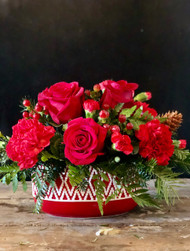 Delight them with a Christmas Centerpiece in cozy sweater print filled with red roses, carnations and hypericum nestled in a bed of Christmas greens