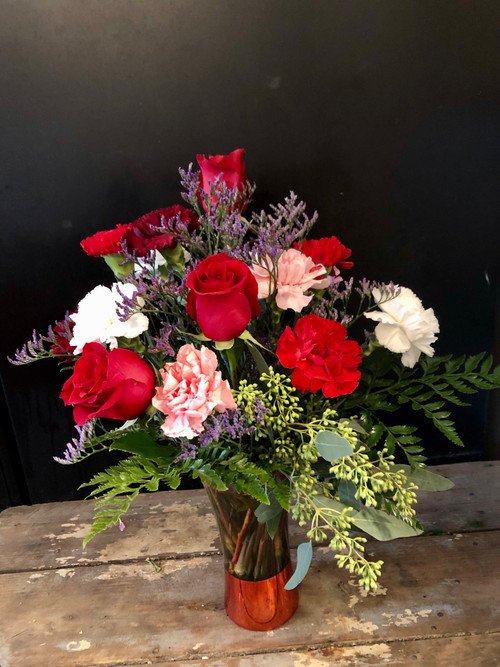 Lovely and long lasting is this combination of red roses and assorted carnations, served in a gorgeous tinted vase with red metallic base and accented with greens.