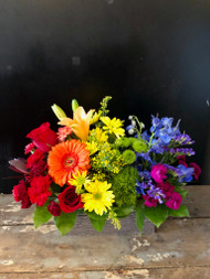 Brighten her world with this unique and colorful fresh floral arrangement in colors of the rainbow.