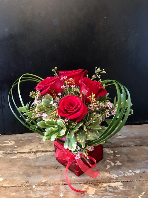 "The best way to say ""I love you"" - 4 red roses nestled in a bed of pittisporum and waxflower and garnished with grasses tied in the shape of a heart."
