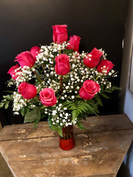 Send her a classic - one dozen pink roses in a cloud of babies breath, nestled in a red metallic and pink collectible vase.
