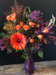 Perfect for Halloween in gorgeous purples and oranges, our mixture of purple stock and waxflower is set off with orange spray roses and a pop of orange in a gerber daisy.  All gathered together in a purple vase.  Our most popular arrangement this fall.