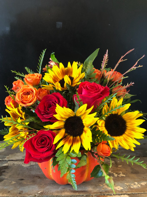 Delightful collection of red and orange roses amid sunny sunflowers arranged in our collectible orange ceramic pumpkin