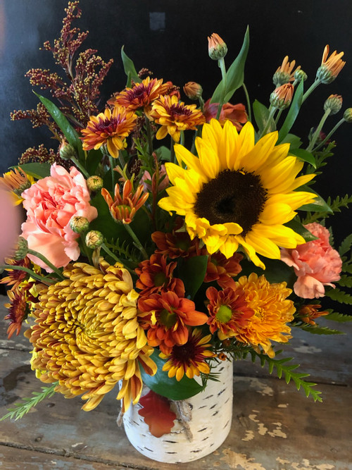 What better way to send a thought than this collection of sunflowers and fall colors in a collectible birch container accented by an oak leaf?