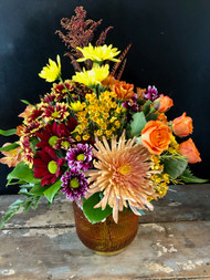 A collection of the brightest fall mums and roses in a collectible orange glass lantern garnished with gold banks and a gold oak lief is sure to brighten someone's day.
