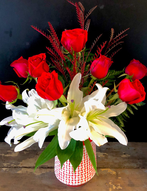Charm someone with Deep red roses and pure white oriental lilies nestled in Christmas greenery in a collectible red and white ceramic vase