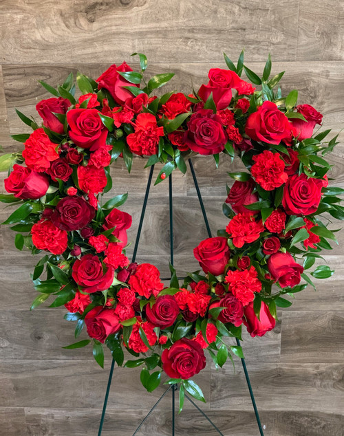 """Express your heartfelt sentiments  with this large heart full of fresh roses and carnations displayed on easel.  Shown in classic red on 18"""" form - actual width 24"""".  Can be done in your choice of color and sized up to 22"""" form with choice of luxury."""