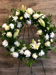 A serene tribute will be paid when sending this all white wreath containing lilies, roses, and mums