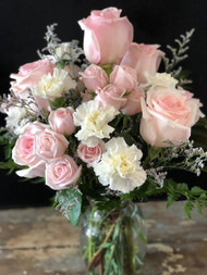 Send a light and airy bouquet of light pink roses and spray roses interspersed with with carnations and limonium.