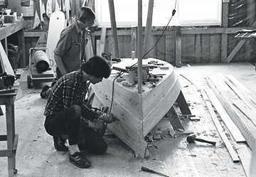 The Maine Skiff is traditionally built in an inverted position. If you happen to be working on a wooden floor, that makes fastening everything down a snap (especially these days with the widespread use of coarse threaded drywall screws and cordless screwdrivers). The boat in this photo was built by the two 14-year-olds you see working on the planking. They spent 47 hours on the project and sold their boat to a local fisherman the day after they finished painting her.