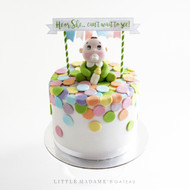 colourful gender reveal cake with baby figurine