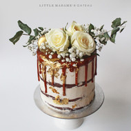 Rustic white and gold drip cake with flowers