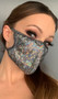 Shimmer face mask with metallic dot design. Elastic straps go around the back of the head to avoid discomfort to your ears. Straps do not tie, you just pull the mask down over your head for a snug fit. Double layered, the inside is cloth lined. Made in the USA.