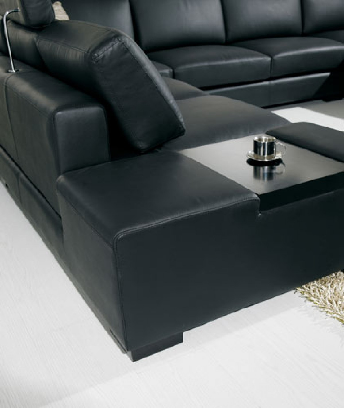 A close up shot of the Amadeo Nero Sectional Available At AdvancedInteriorDesigns.com. This Black Sectional also features lights.