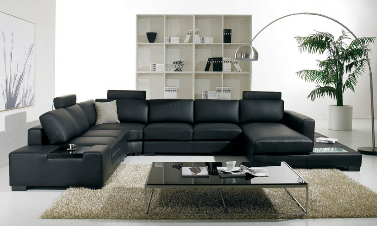 A Contemporary Sectional That Is Upholstered In A Black Bonded Leather. The Contemporary Sectional also features a light.