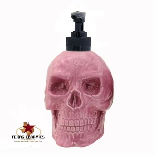 Bright pink skull soap dispenser with black pump unit.