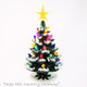 Green ceramic Christmas tree with snow on the branches, color lights and gold star