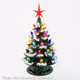 Small ceramic tree with snow tip branches, color lights and modern red star.